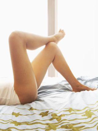 perempuan legs crossed laying in bed