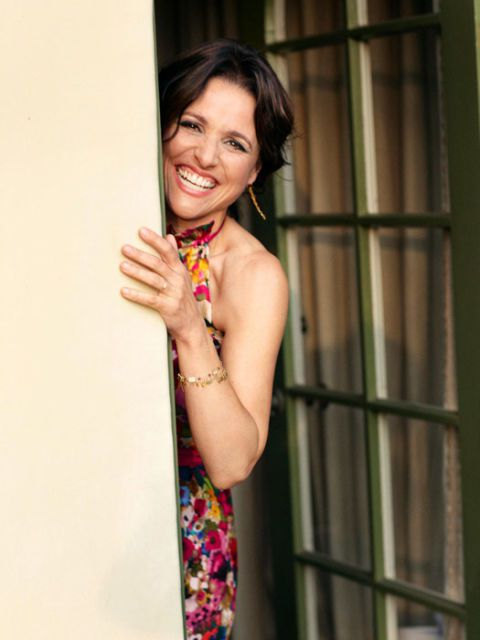 aktorka julia louis-dreyfus peeking behind a door and laughing