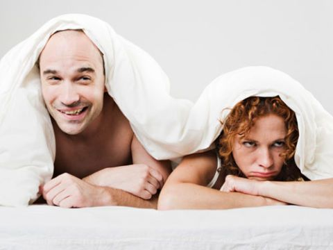 tersenyum man and unhappy woman under white cover in bed