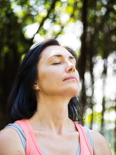 Fechar-se Caucasian adult woman face. Action breathing and relaxing in park. In yoga or meditation activities.